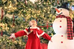 Den lyckliga flickan för det lilla barnet i santa dräktklänning har gyckel och lek med snö på vintertid mot julbakgrund glatt arkivfoto