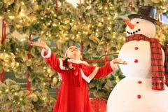 Den lyckliga flickan för det lilla barnet i santa dräktklänning har gyckel och lek med snö på vintertid mot julbakgrund glatt royaltyfria bilder