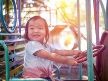 Den lyckliga flickan för den lilla ungen som spelar på karusell i, parkerar på en mycket solig dag Förtjusande barn som spenderar royaltyfri foto