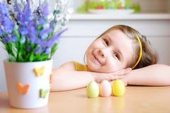 Den lyckliga flickan firar påsk hemma Arkivfoton