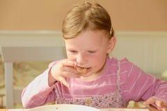 Den lyckliga flickan har ett mellanmål i köket En gullig liten flicka äter chokladpralin spred på bröd En liten flicka med Fotografering för Bildbyråer