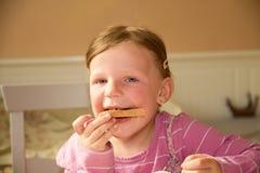 Den lyckliga flickan har ett mellanmål i köket En gullig liten flicka äter chokladpralin spred på bröd En liten flicka med Arkivbild