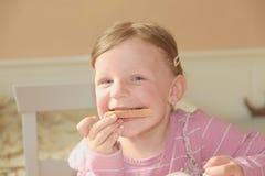 Den lyckliga flickan har ett mellanmål i köket En gullig liten flicka äter chokladpralin spred på bröd En liten flicka med Arkivfoton