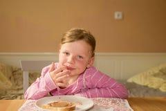 Den lyckliga flickan har ett mellanmål i köket Gulliga små leenden för en flicka En liten flicka med chokladpralinfläckar på fram Arkivfoton