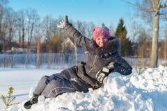 Den lyckliga flickan har gyckel med snö Fotografering för Bildbyråer