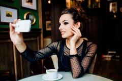 Den lyckliga flickan har koppen av grönt te och taselfie inomhus Royaltyfri Bild