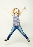 Den lyckliga flickan hoppar på en vit bakgrund Royaltyfri Foto