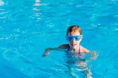 den lyckliga flickan i blått rullar med ögonen simning i simbassängen Arkivbild