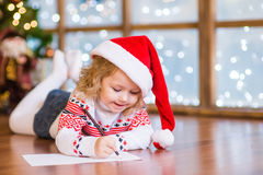 Den lyckliga flickan i röd julhatt skrivar brevet till Santa Claus Arkivfoto