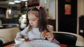 Den lyckliga flickan i rosa färgkläder äter aptitretande pizza i pizzeria stock video