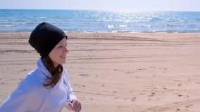 Den lyckliga flickan joggar på jogger för stående för havssandstrand, körnings somsporten passade utomhus arkivfilmer