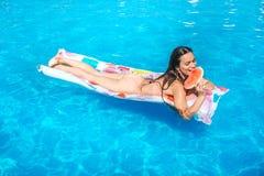 Den lyckliga flickan ligger på luftmadrassen och äter stycket av vattenmelon Hon ler Flickan är i simbassäng arkivfoton