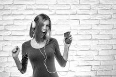 Den lyckliga flickan lyssnar till musik royaltyfri fotografi