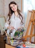 Den lyckliga flickan målar på kanfas med olje- färger Royaltyfri Foto