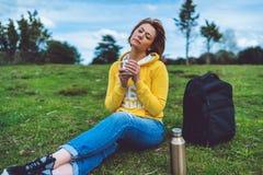 Den lyckliga flickan med ögon stängde att rymma i handkopp av varmt te på grönt gräs i det fria som naturen parkerar, härlig kvin royaltyfria bilder