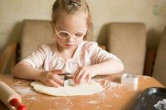 Den lyckliga flickan med Down Syndrome bakar kakor Royaltyfri Bild