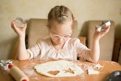 Den lyckliga flickan med Down Syndrome bakar kakor Arkivfoto