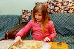 Den lyckliga flickan med Down Syndrome bakar kakor Arkivbild