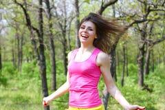 Den lyckliga flickan med ett överhopprep i en sommar parkerar Royaltyfri Foto