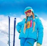 Den lyckliga flickan med hennes berg skidar Royaltyfri Foto