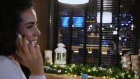 Den lyckliga flickan med lockigt hår i en restaurang talar på telefonen stock video