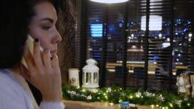 Den lyckliga flickan med lockigt hår i en restaurang talar på telefonen och leende stock video