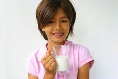 den lyckliga flickan mjölkar arkivbild