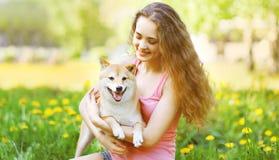 Den lyckliga flickan och hunden i solig sommar parkerar Arkivfoto