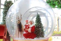 Den lyckliga flickan och modern för litet barn i santa dräktklänning har gyckel i stort vintersnöjordklot med renen på jultid gla arkivbild