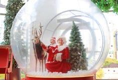 Den lyckliga flickan och modern för litet barn i santa dräktklänning har gyckel i stort vintersnöjordklot med renen på jultid gla royaltyfri foto