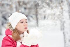 Den lyckliga flickan på en frostig vinter går på gataslag snöar från händer Arkivbild