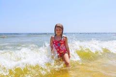 den lyckliga flickan på ett tropiskt strandhav har gyckel med färgstänk Arkivbilder