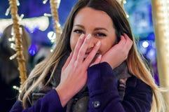 Den lyckliga flickan på gatan dekorerade för jul som ser upp Arkivfoton