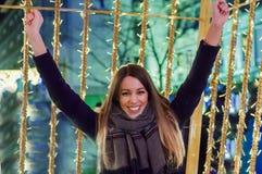 Den lyckliga flickan på gatan dekorerade för jul som ser upp Arkivbild