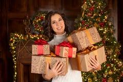 Den lyckliga flickan rymmer många julgåvor Arkivbild