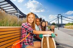 Den lyckliga flickan rymmer skateboarden på bänk med flickor Royaltyfria Bilder
