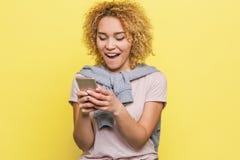 Den lyckliga flickan ser skärmen och le för telefon` s Hon är upphetsad och lycklig Isolerat på gul bakgrund arkivbild