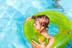 Den lyckliga flickan simmar i en pöl in på den gröna livpreserveren fotografering för bildbyråer