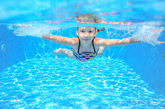 Den lyckliga flickan simmar i undervattens- aktiv ungesimning för pöl och hagyckel Royaltyfri Fotografi