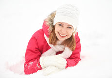 Den lyckliga flickan skrattar, medan ligga på den insnöade vintern utomhus royaltyfria foton