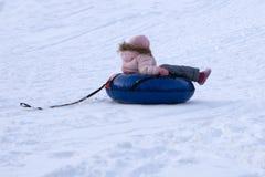 Den lyckliga flickan som är sluttande på snöröret skidar på, semesterorten på solvinterdagen royaltyfri bild