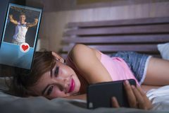 Den lyckliga flickan som ligger på säng som ler och flörtar på socialt massmedia app som för internet använder hållande ögonen på Arkivbilder