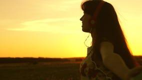 den lyckliga flickan som lyssnar till musik och dansar i str?larna av en h?rlig solnedg?ng parkerar in Härlig flicka i hörlurar o stock video