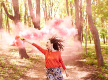 Den lyckliga flickan som skrattar och kör med rosa färgfärgrök, bombarderar i skog arkivfoto