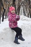 Den lyckliga flickan spelar i parkera i vintern royaltyfri foto