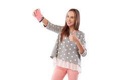 Den lyckliga flickan tar selfie och visar ok gest som över isoleras Arkivbild