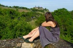 Den lyckliga flickan vaggar på att koppla av med en sikt till druvafältlandcape och Festungen eller fortet Marienberg i bakgrund Arkivbild