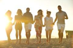 Den lyckliga folkgruppen har roligt och running på strand Arkivbild