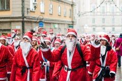 Den lyckliga folkuppklädden som santas kör till och med den gamla staden av Stockholm som deltar i välgörenhethändelsen Stockholm Arkivbild