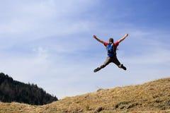 Den lyckliga fotvandraren hoppar upp Royaltyfri Fotografi